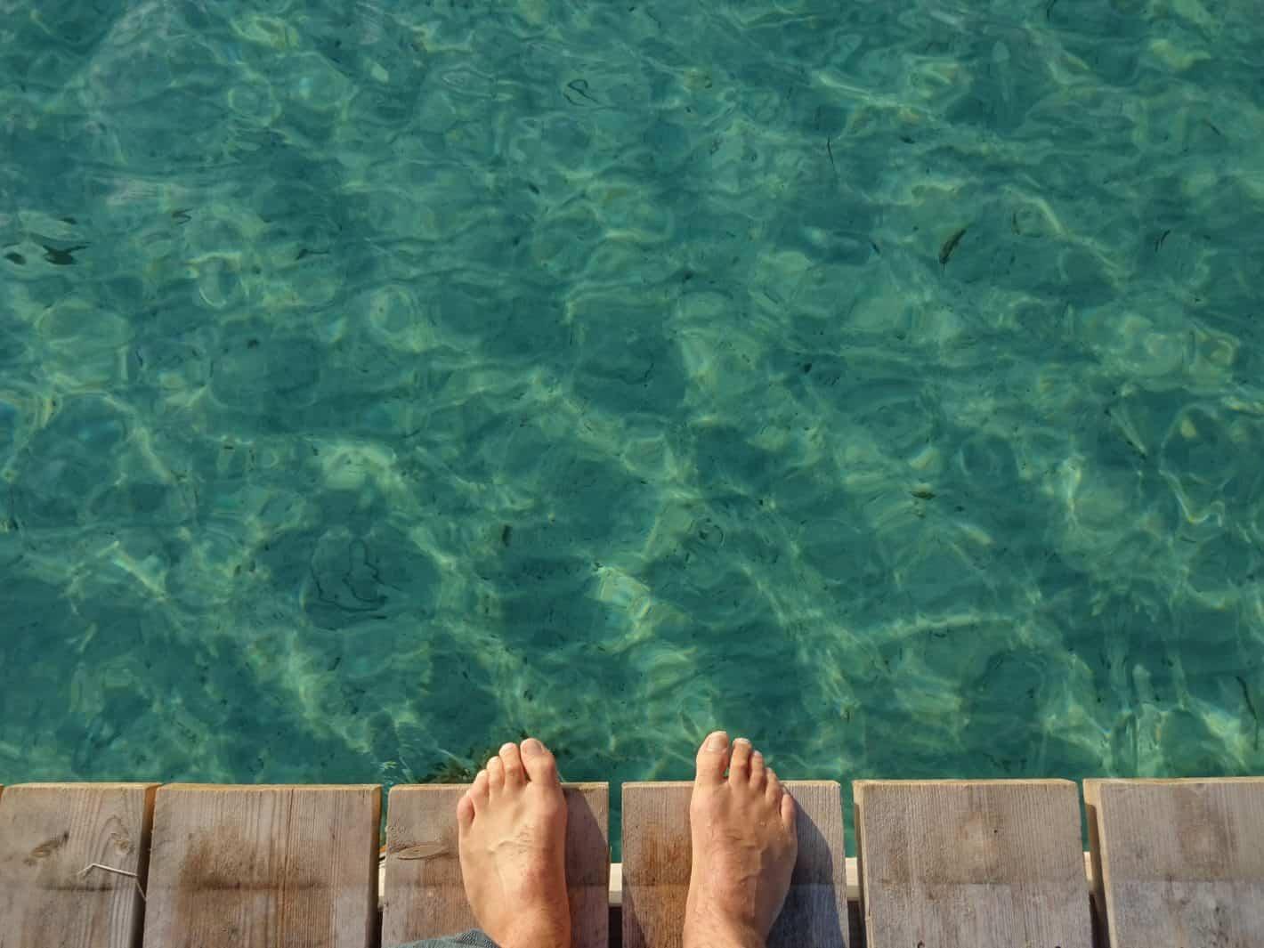 Nackte Füße auf einem Holzsteg über türkisen Mittelmeer