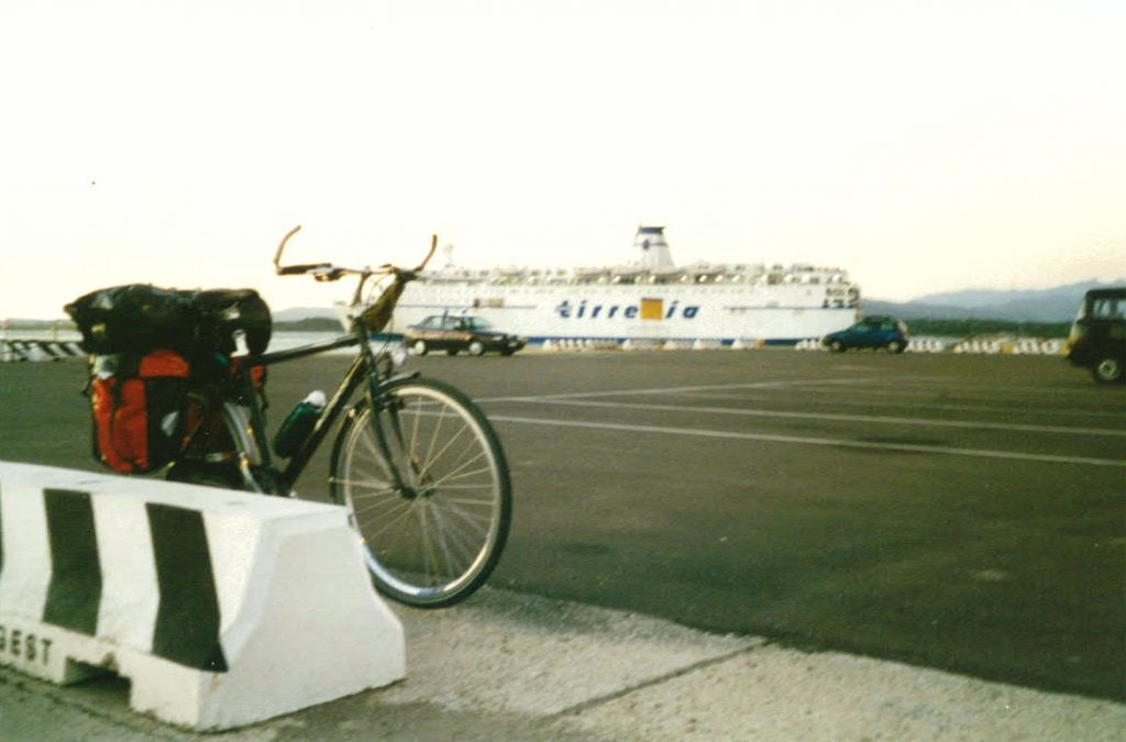 Rad eines Radreisenden mit Faehrhafen in Oblie Sardinien im Hintergrund