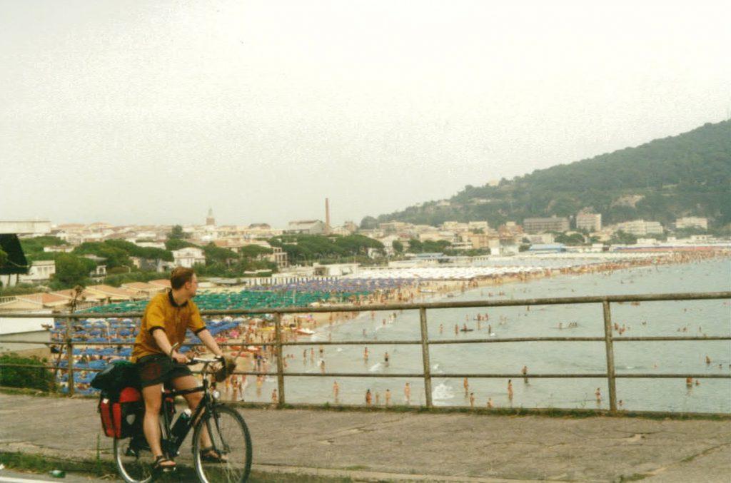Radreisender mit Sonnenschirme-Feldern im Hintergrund an der italienischen Ostkueste