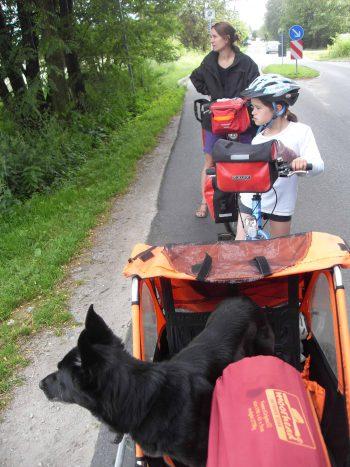 Familie Radreisender mit Hund im Fahrradanhaenger